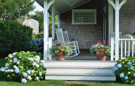 white porch and chairs with hydrangeas